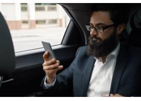 一名商人在使用智能手机乘汽车旅行在后座_7120585