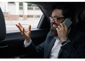 一名商人在使用智能手机乘汽车旅行在后座_7120587