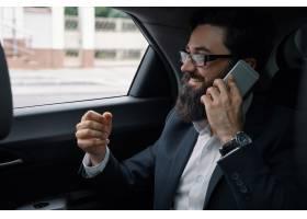 一名商人在使用智能手机乘汽车旅行在后座_7120588