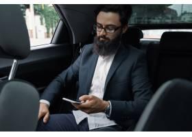 一名商人在使用智能手机乘汽车旅行在后座_7120589