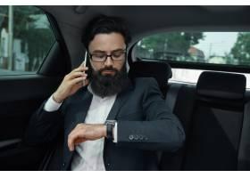 一名商人在使用智能手机乘汽车旅行在后座_7120590