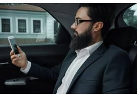 一名商人在使用智能手机乘汽车旅行在后座_7120591