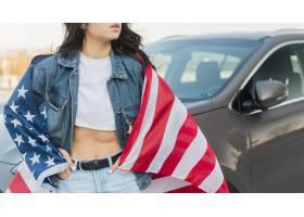 佩带大美国旗子的中间射击妇女在汽车附近_7968586