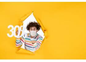 在拿着在黄色颜色购物健康covid的面具的前_16384480