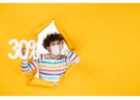 在拿着在黄色颜色购物健康covid的面具的前_16384597