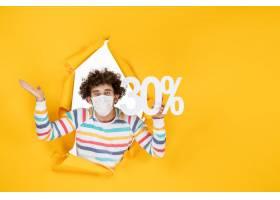 在拿着在黄色颜色购物健康covid的面具的前_16384608
