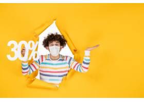 在拿着在黄色颜色购物健康covid的面具的前_16384619