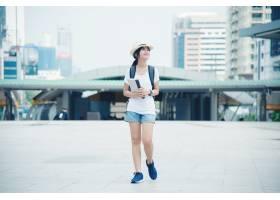 有背包的愉快的微笑的亚裔学生女孩在城市背_4835550
