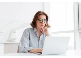 玻璃和镶边衬衣的迷人的女实业家与便携式计_7725015