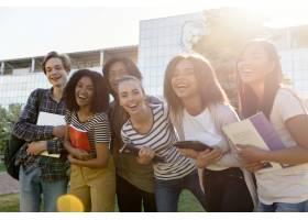 站立不同种族的小组年轻快乐的学生户外_7571533