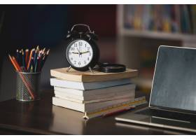 书膝上型计算机铅笔在木桌上的时钟在_5473635