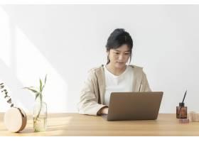亚裔妇女在家使用膝上型计算机_15667791