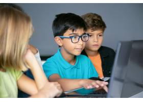 键入在膝上型计算机键盘和同学的亚裔男孩坐_10579174