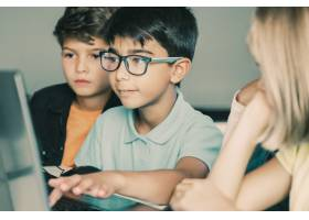 键入在膝上型计算机键盘和同学的亚裔男孩坐_13145733