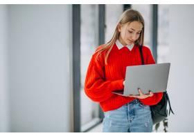 有站立在走廊的膝上型计算机的女学生窗口_7376227