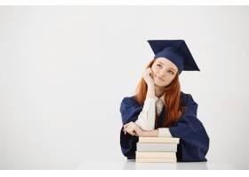 微笑的毕业生妇女微笑着坐与书_9028620