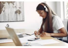 坐在桌上的年轻学生和使用膝上型计算机_5913128