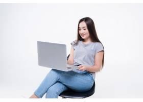 亚裔妇女谈话在电话和看膝上型计算机当坐_13622476