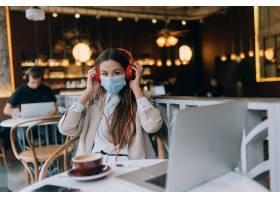 坐在有耳机冠状病毒爆发的一家咖啡店的女孩_15684752
