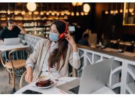 坐在有耳机冠状病毒爆发的一家咖啡店的女孩_16597920