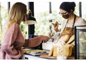 妇女佩带的面具在咖啡馆餐馆covid的食物19_13311663