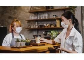 年轻女性Barista穿面具面膜服务带走热咖啡_15116357