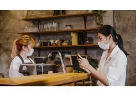 年轻女性戴面罩自助服务使用手机在餐厅没有_15116362