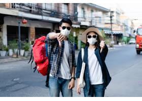 年轻背包客在面罩和太阳镜的夫妇做一个禁止_15642289