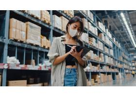 佩带的面罩仓库的年轻亚裔女实业家经理使用_14407663