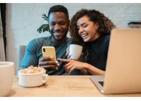 使用一个手机的年轻夫妇当一起吃早餐在家_16234238