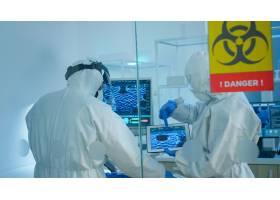 覆盖的科学家站立在玻璃墙后面工作在实验室_15786011