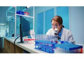 检查病毒开发的科学家团队使用显微镜分析结_15785424