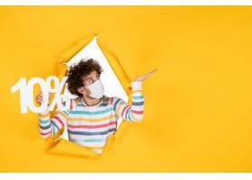 正面图年轻男性在无菌面具举行在黄色照片健_16385267