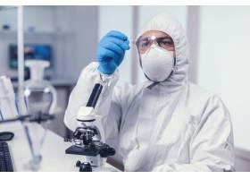看显微镜幻灯片的科学家在冠状病毒期间穿戴_15799183