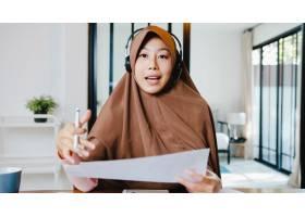 穆斯林夫人穿戴耳机使用计算机笔记本电脑与_15114220
