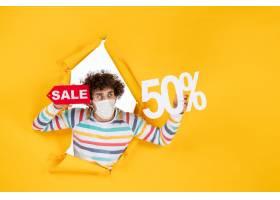 在举行在黄色购物covid的面具的前视图年轻_16384863