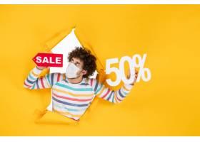 在举行在黄色购物covid的面具的前视图年轻_16384869