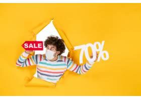 在举行在黄色购物covid的面具的前视图年轻_16385145