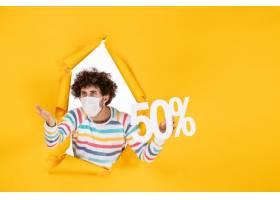 在拿着在黄色购物健康大流行covid的面具的_16384884
