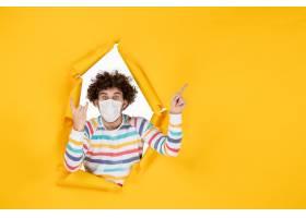 前视图年轻男性在无菌面具在黄色被剥去的颜_16387187