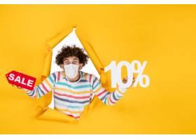 前面视图年轻男性在举行和销售在黄色照片健_16381571