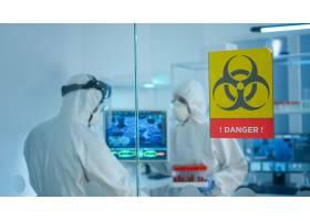 PPE衣服的担心的科学家谈论在玻璃墙后面工_15786003