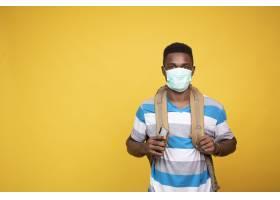 与佩带facemask的背包的年轻非洲男性   Co_17234794