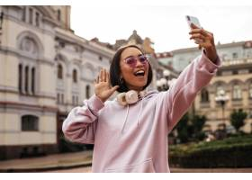 粉红色的连帽衫和时髦的太阳镜的凉快的青少_16083467
