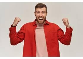 红色衬衣的快乐的可爱的年轻有胡子的人看起_14092066