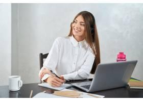 耳机的正面妇女学习在膝上型计算机_14057588