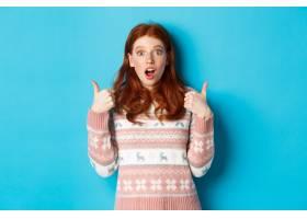 被印象深刻的毛线衣的红头发人女孩显示竖起_16788095