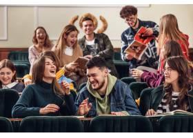 坐在演讲厅的快乐的愉快的学生小组在教训前_9708333