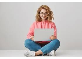 微笑的女学生文字文章坐与膝上型计算机在_9798944