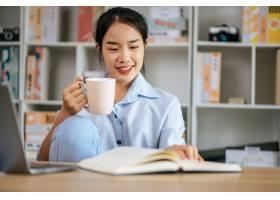 快乐的年轻俏丽的妇女坐和使用便携式计算机_17626442